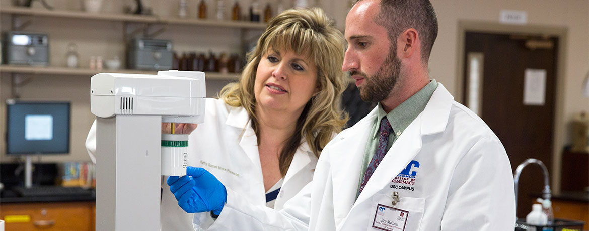 a pharmacy student working with a professor in the lab