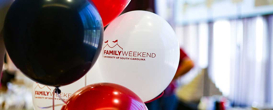 black, white and garnet balloons that read Family Weekend