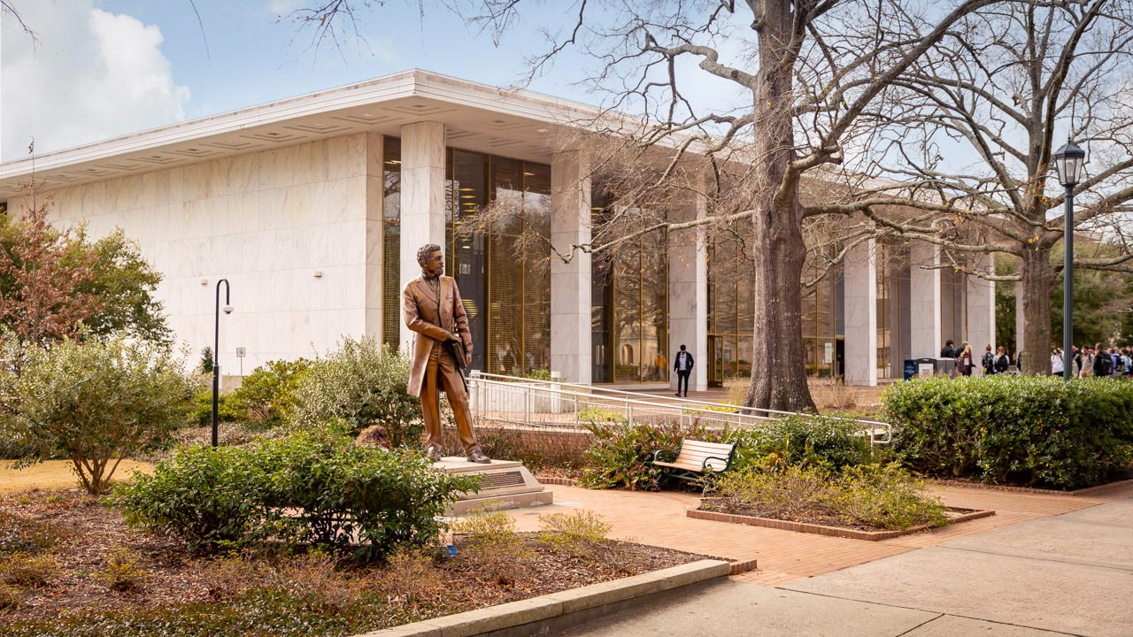 The bronze Richard T. Greener statue sits in front of the Thomas Cooper Library.