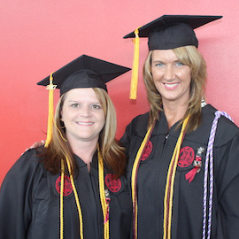 Kristal Tribble and Tina Williamson pose in their caps and gowns after graduating from the online RN to BSN program.