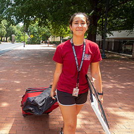 New student pulls her suitcase behind her on Greene Street as she moves in.