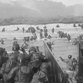 soldiers exiting boats into the beach during WWII