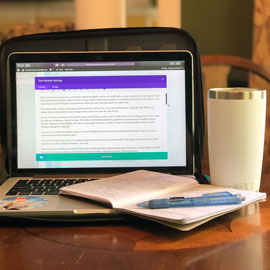 A photo by Joseph Leonard showing his working from home set up. It includes his laptop, a cup, a notebook and a pen.