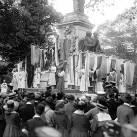 women with banners stand by a monument in Washington D.C. in 1918 to advocate for women's suffrage